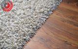 White shaggy carpet on brown wooden floor detail
